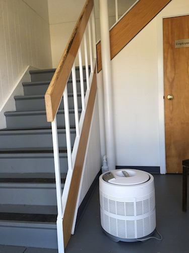 A round white HEPA filter sitting on a gray floor with a staircase next to it.
