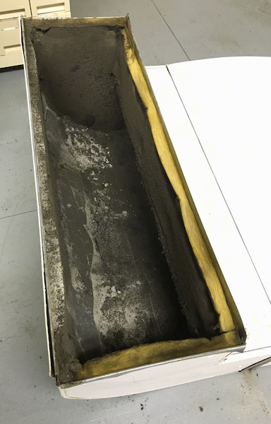 A section of a fiberglass lined duct with lots of black dirt all over the inside laying on a floor after being removed