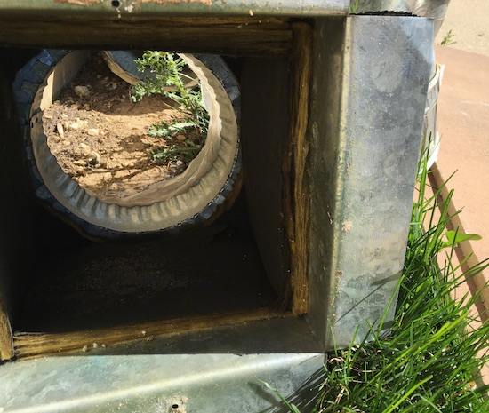 A section of a fiberglass lined duct laying outside after being removed