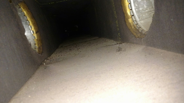 A view from the inside of a fiberglass lined duct with two air ducts shooting off to the left and right