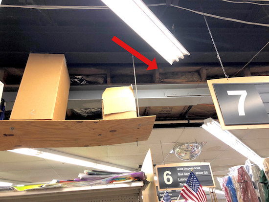 The ceiling of a store where the drop ceiling ends and a medal ceiling begins with exposed bats of fiberglass visible.