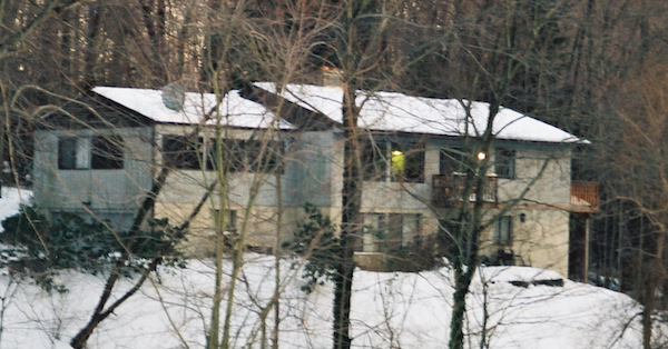 A long gray house on a snow covered hill with trees in front.