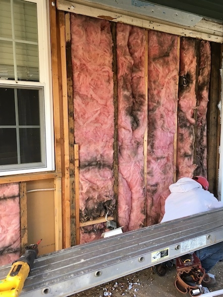 Pink fiberglass insulation on the outside of a house under a porch with black mold and dirt lines in it. There is a window on the left. There is a person in a red hat and gray shirt kneeling down in front of the fiberglass.