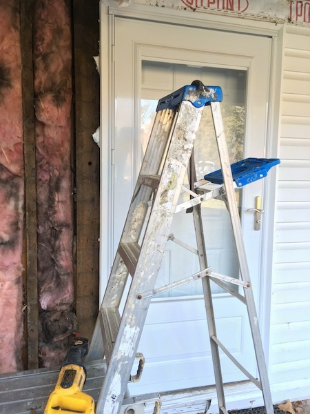 A silver ladder in front of the storm door of a white house under a porch with pink moldy fiberglass off to the left in the wall.