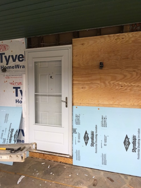 The front of a house with a white door with Tyvek paper on the left and plywood and blue styrafoam on the right. It is under a porch that has a green roof and a stone floor.