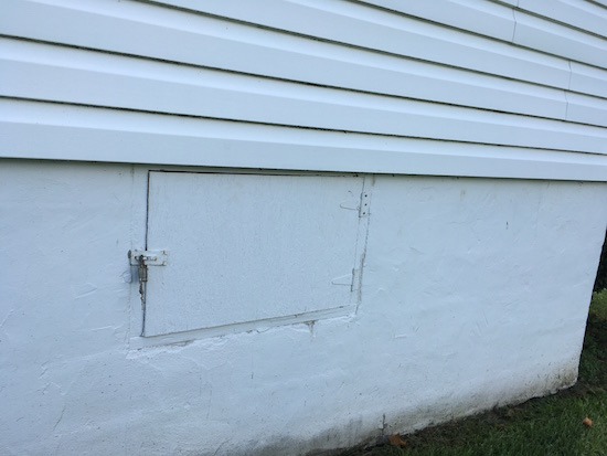 A crawl space door on the outside of a white farmhouse