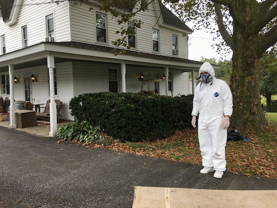 A man in a hazmat suit and gas mask standing in front of a white farm house with a stone wrap around porch.