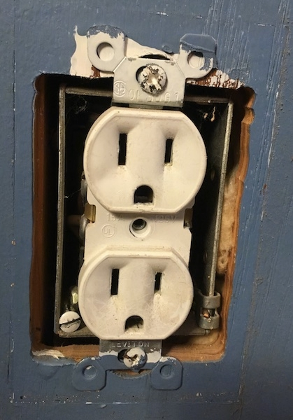 Close up of an electrical outlet that has the cover removed showing yellow fiberglass in the wall.