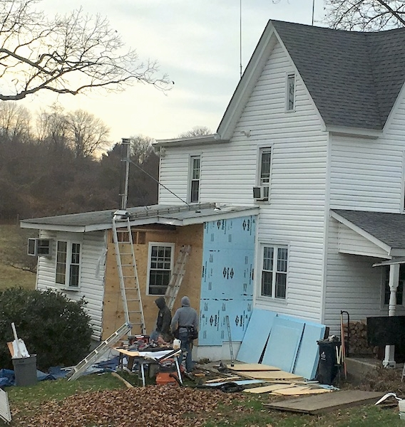 A white farm house with the siding removed from part of the house with wood and blue styrafoam showing with tools and construction materials all around the yard.