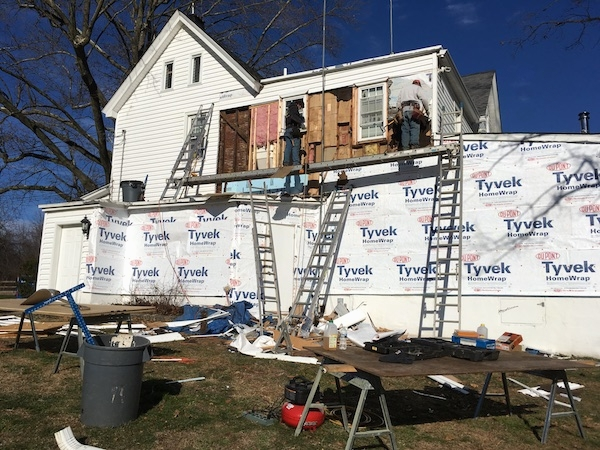 A white farm house with the siding removed on a large part of the house with Tyvek paper showing on the first floor. Up on the second floor are two people removing pink fiberglass insulation from the walls.