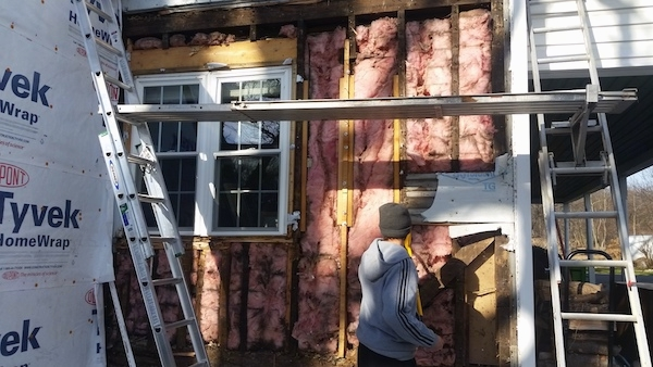 Close up of a white farm house with some of the siding removed showing the pink fiberglass insulation. There is a person dressed in gray standing in front of it.