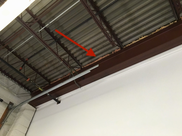 An arrow pointing to fiberglass insulation along a beam in an industrial building