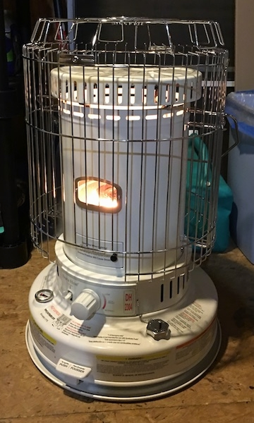 A round white kerosene heater lit in a room that has a wood floor. There is a safety cage built around the heater.