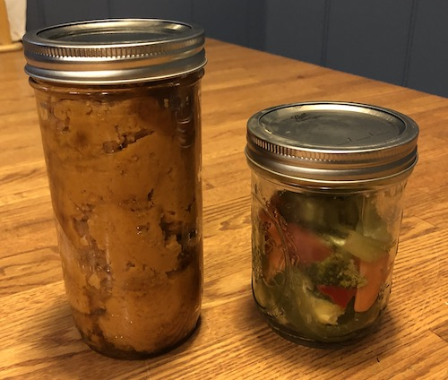 Two mason jars side by side, one with pumpkin filling and the other with veggies sitting on a brown wooden table
