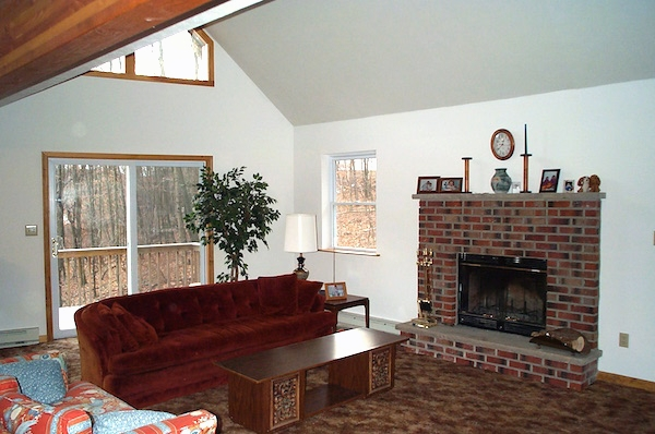 A living room with a fireplace, rust colored couch, red and blue love seat, wooden coffee table, tan carpets and large windows letting a lot of light in.