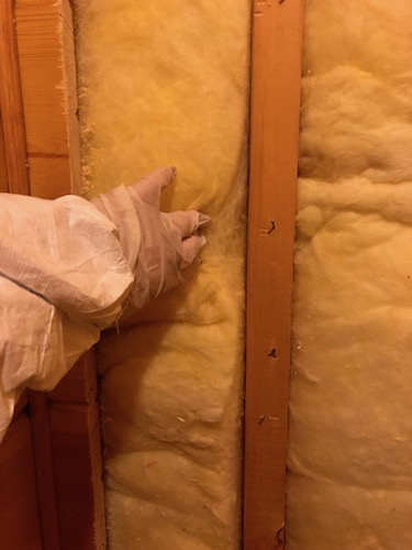 A person wearing a white hazmat suit wearing a rubber glove reaching out their hand to touch yellow fiberglass batt insulation that is behind a hole in a wall.