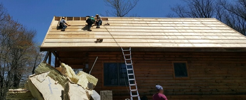 Three men up on the roof of a wooden log cabin putting down new plywood. There is a fourth man standing on the ground next to a very large 8 foot pile of yellow fiberglass batts.