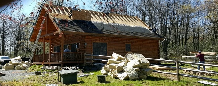 Front side view of a wooden log cabin with shingles remaining on the lower end of the roof. They were removed from the top near the peak and there is a large pile of fiberglass on the ground in front of the cabin and a second pile on the side of the cabin.