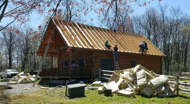 The front side view of a wooden log cabin with four men up on the roof after the shingles and plywood had been removed. There is a very large pile of fiberglass on the side of the cabin with a second pile in front of the cabin.