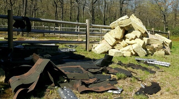 A large pile of thick yellow fiberglass batts laying on the ground in front of a pile of black roof shingles in front of a split rail fence.