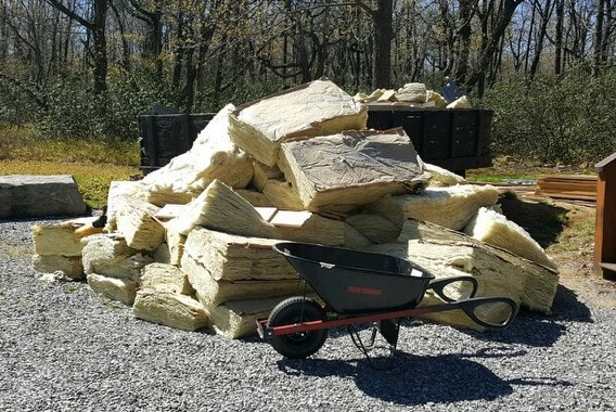 A large pile of yellow fiberglass batts laying in the stone gravel driveway with a wheel barrow sitting in front of it.
