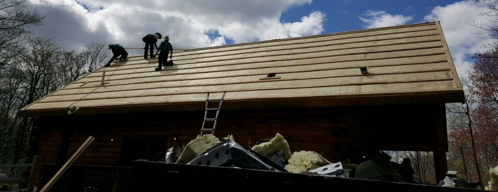 Three men on top of a log cabin roof nailing up new plywood. There is a large dumpster full of yellow fiberglass batts in front of them.