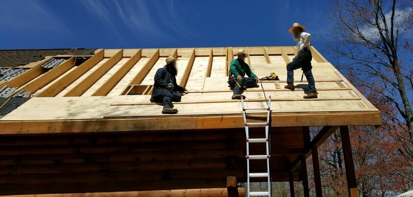 Three Amish men in straw hats on top of a log cabin roof that has had its shingles and plywood removed. The men are putting new plywood back.