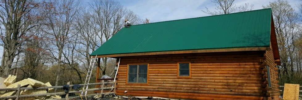 The side of a log cabin with a green tin roof. There is a man on the top of the peak of the roof and a pile of yellow fiberglass on the ground.