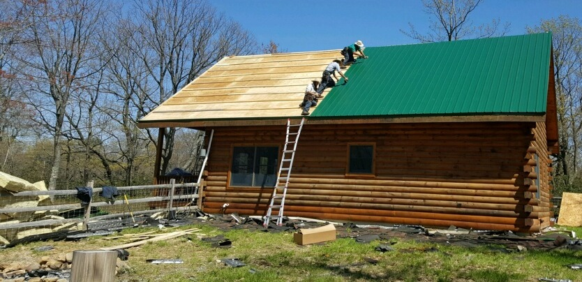 A wooden log cabin with half of the roof green tin and the other half plywood. There are four men on the roof laying down the green tin and a pile of yellow fiberglass on the left of the image on the ground. The cabin has a split rail fence around the back yard.