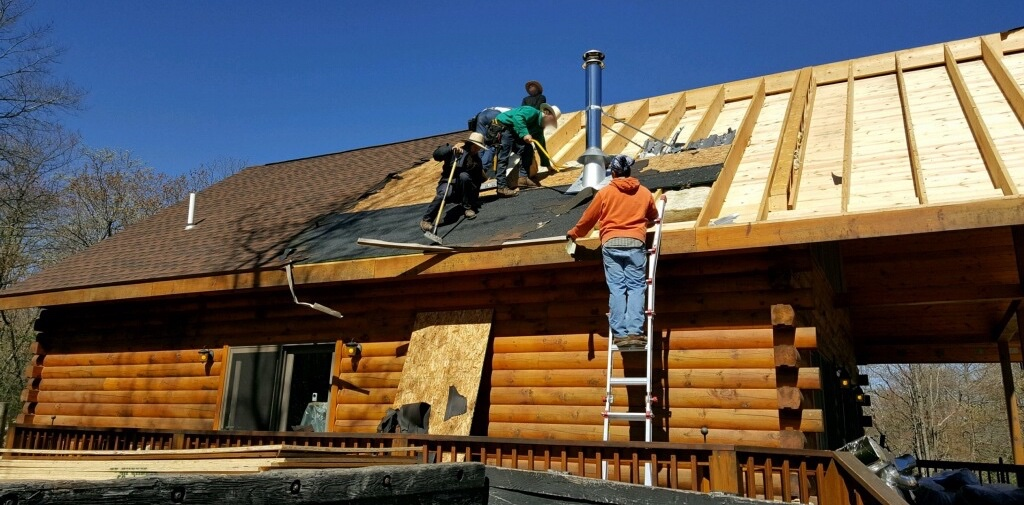 Three Amish men on the roof of a log cabin ripping up shingles with a fourth man in an orange sweat shirt standing on a ladder that is leaning against the side of the house.