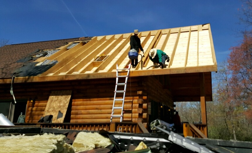 Two Amish men on the roof of a log cabin standing inside of the wooden bays after the shingles and plywood had been removed from that half of the roof. There is a ladder leaning against the side of the building.