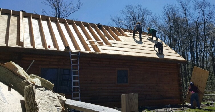 The side of a log cabin with the roof shingles taken off exposing the wood under. New plywood is being put down and there is a large pile of yellow fiberglass in front of the cabin on the ground. Three men are up on the roof.