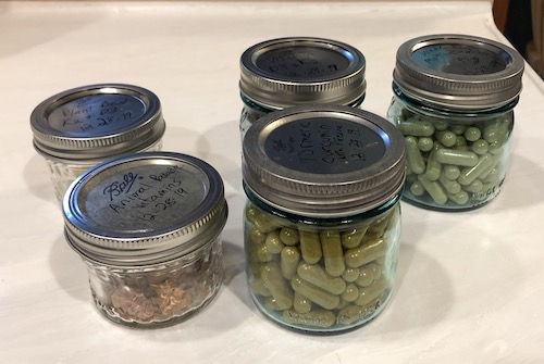 Five little glass mason jars with metal lids full of vitamins