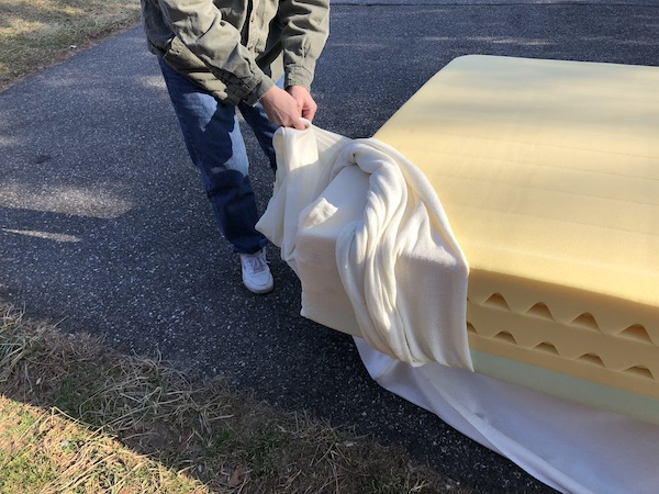 A man removing the fiberglass cover from a memory foam mattress outside on a driveway.