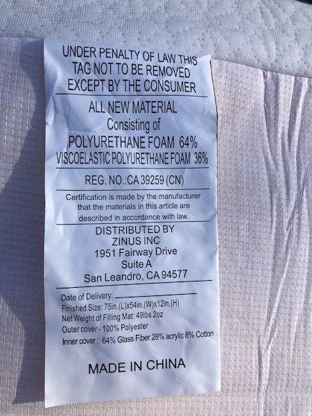 A memory foam mattress label connected to a white bed.