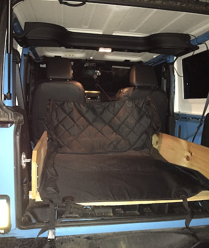 The back of a blue Jeep JK car with a wooden box and a dog liner covering it.