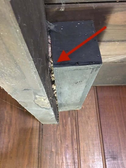a red arrow pointing to a crack between a wooden beam and wooden box in a ceiling with fiberglass exposed in the crack