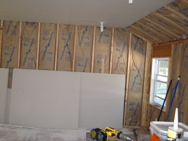 A studded wall with the paper side of fiberglass batts showing with drywall leaning against the wall. There are tools all around the room.