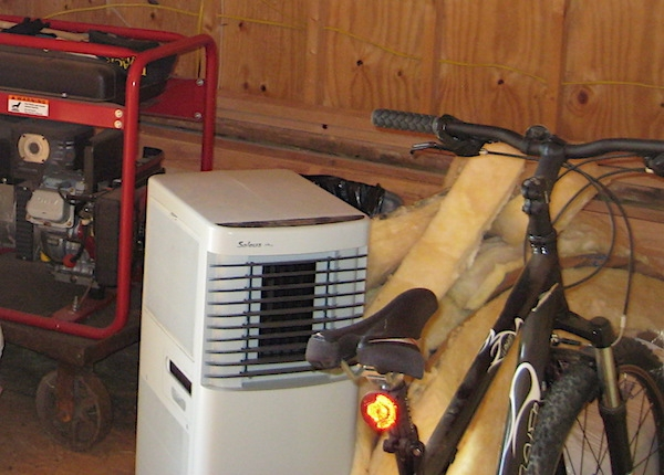 A black bicycle parked next to a pile of yellow fiberglass scraps. There is a white dehumidifier and a red generator next to it.