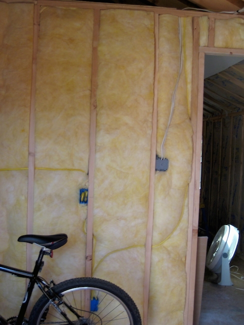 A room with yellow fiberglass in an open wall with electrical outlets and wires with a black bicycle parked in front of it. There is a white fan on the floor in the other room.