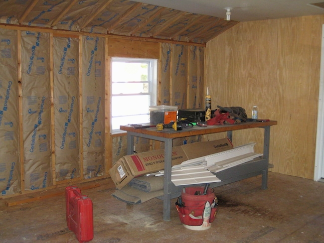 A room being built with fiberglass batts lining the studded wall up to the ceiling where the drywall was put up. There is a work bench and tools in front of the wall.