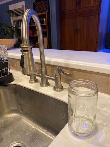 A kitchen sink with a glass jar that has a little bit of soap in it
