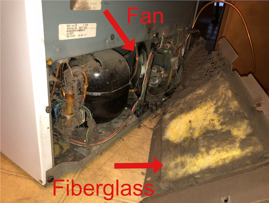 The back bottom of a refrigerator with the panel taken off and a red arrow pointing to a cooling fan with the red letters Fan written next to it and another red arrow pointing to a yellow panel of fiberglass with the red words written Fiberglass.