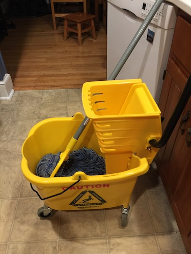 A yellow industrial size mop and bucket in a kitchen of a house