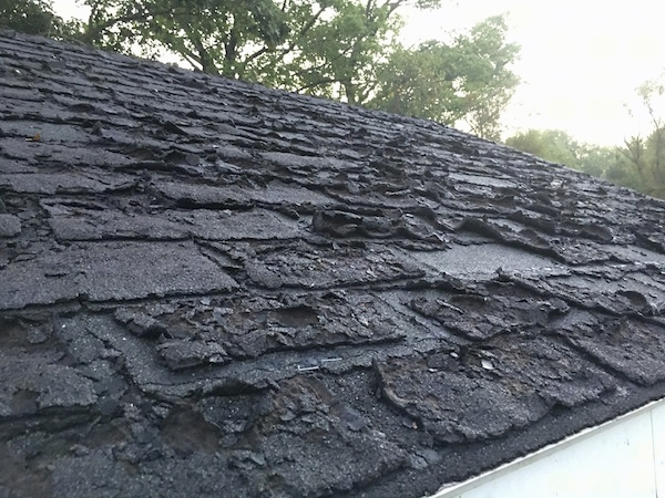 A very warn out black asphalt roof that is cracking and curling.