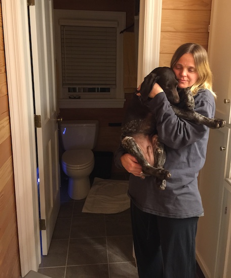A female with blonde hair holding a little German Shorthair Poiner puppy in a wooden bathroom with a gray tiled floor