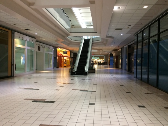An empty shopping mall with an escalator and closed stores. There is a bright sky light letting in the sunlight.