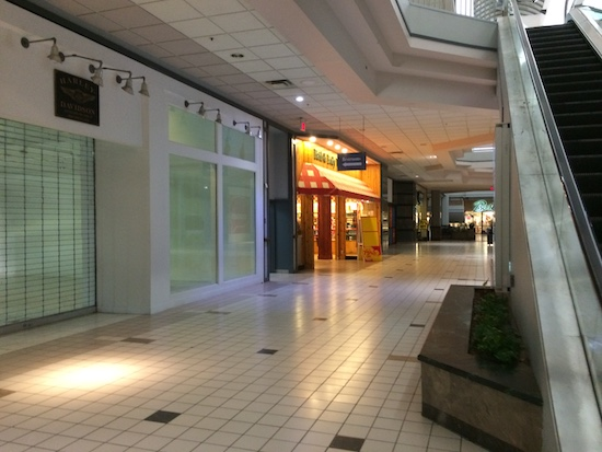The isle in an empty shopping mall with closed stores, and a shiny white tiled floor. There is a bath soap store with a red and white awning and bright lights but no people.