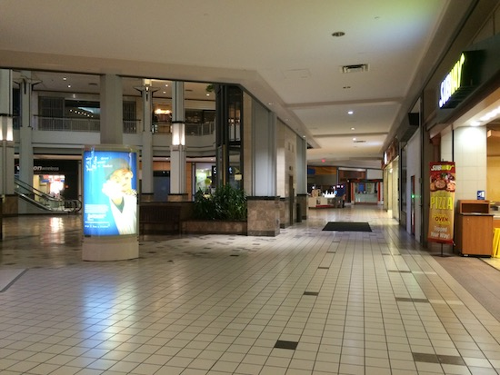 A big empty shopping mall with closed stores and a staircase in the background. It looks like a ghost town.