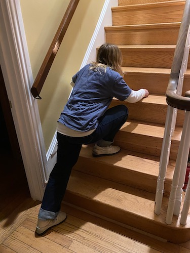 A girl with blonde hair wearing a blue shirt and jeans leaning with her right foot on the second step on a staircase and her left foot on the floor below.